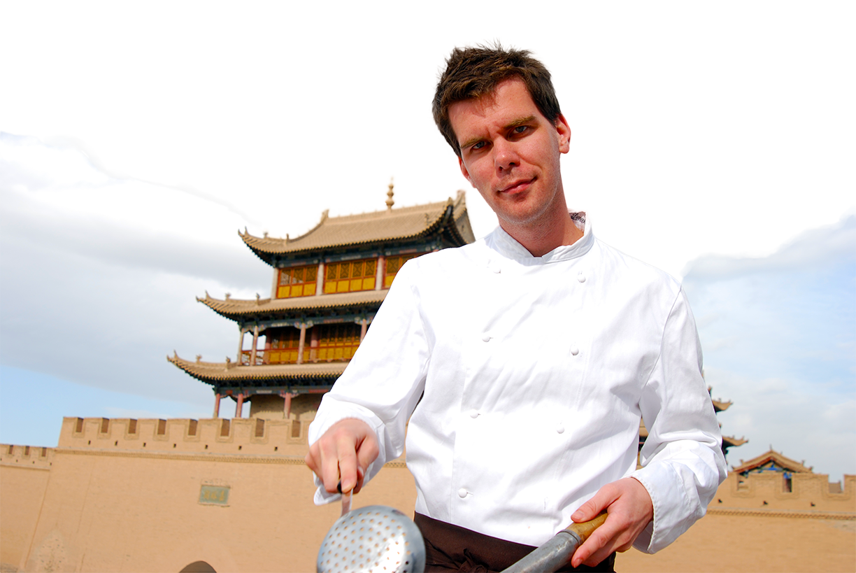 James cooking in front of Chinese castle.